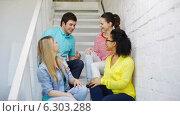 Купить «Smiling students sitting on stairs and talking», видеоролик № 6303288, снято 15 апреля 2014 г. (c) Syda Productions / Фотобанк Лори