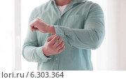 Купить «Man unbuttoning his sleeve at home», видеоролик № 6303364, снято 7 мая 2014 г. (c) Syda Productions / Фотобанк Лори