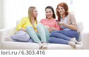 Купить «Three smiling teenage girls watching tv at home», видеоролик № 6303416, снято 8 мая 2014 г. (c) Syda Productions / Фотобанк Лори