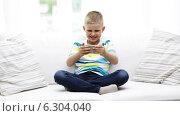 Купить «Smiling boy playing with smartphone at home», видеоролик № 6304040, снято 12 июня 2014 г. (c) Syda Productions / Фотобанк Лори