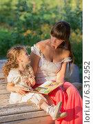 Купить «Мама и дочка читают и обсуждают книгу на лавочке в парке», фото № 6312952, снято 18 июля 2014 г. (c) Алексей Назаров / Фотобанк Лори