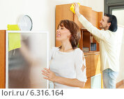 middle-aged couple wiping the dust at home. Стоковое фото, фотограф Яков Филимонов / Фотобанк Лори