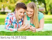 Купить «smiling couple with smartphone and earphones», фото № 6317532, снято 7 июля 2014 г. (c) Syda Productions / Фотобанк Лори