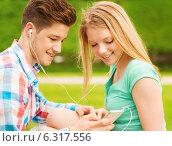 Купить «smiling couple with smartphone and earphones», фото № 6317556, снято 7 июля 2014 г. (c) Syda Productions / Фотобанк Лори