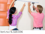 Молодая пара выбирает место для картины на стене. Стоковое фото, фотограф Okssi / Фотобанк Лори