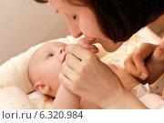 Купить «Молодая мама нежно целует ручку маленького ребенка», фото № 6320984, снято 11 июля 2014 г. (c) Виктор Топорков / Фотобанк Лори