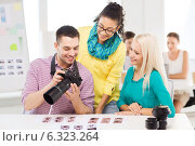 Купить «smiling team with photocamera working in office», фото № 6323264, снято 17 мая 2014 г. (c) Syda Productions / Фотобанк Лори