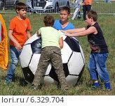 Купить «Дети катят огромный футбольный мяч лежит в сторону ворот», фото № 6329704, снято 24 августа 2014 г. (c) SevenOne / Фотобанк Лори