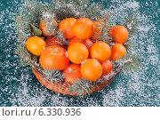Купить «Композиция с мандаринами и еловыми веточками в плетеной корзинке для праздничного стола на зеленом фоне с искусственным снегом», фото № 6330936, снято 31 декабря 2013 г. (c) Александр Волков / Фотобанк Лори