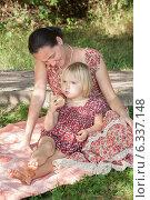 Мама с дочкой сидят на пледе в парке. Девочка держит в руке яблоко, женщина смотрит на нее. Стоковое фото, фотограф Мороз Елена / Фотобанк Лори