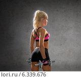 Купить «sporty woman with heavy steel dumbbells», фото № 6339676, снято 8 мая 2014 г. (c) Syda Productions / Фотобанк Лори