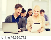 Купить «two smiling students with laptop and tablet pc», фото № 6350772, снято 2 ноября 2013 г. (c) Syda Productions / Фотобанк Лори