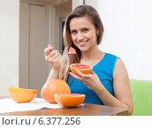 beautiful girl eats grapefruit with spoon. Стоковое фото, фотограф Яков Филимонов / Фотобанк Лори