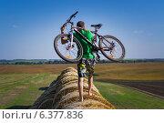 Юноша с великом на тюках соломы (2014 год). Редакционное фото, фотограф Друзюк Олександр Степанович / Фотобанк Лори