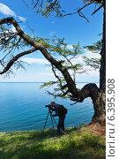Фотограф с камерой на штативе снимает летний пейзаж на берегу Байкала. Стоковое фото, фотограф Виктория Катьянова / Фотобанк Лори