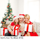 Купить «smiling family holding gift boxes and sparkles», фото № 6402916, снято 26 октября 2013 г. (c) Syda Productions / Фотобанк Лори