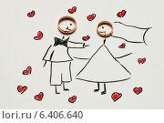 Купить «Два золотых обручальных кольца лежат на детском рисунке с женихом и невесты», эксклюзивное фото № 6406640, снято 12 июля 2014 г. (c) Игорь Низов / Фотобанк Лори