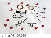 Купить «Два золотых обручальных кольца лежат на детском рисунке», эксклюзивное фото № 6406664, снято 1 августа 2014 г. (c) Игорь Низов / Фотобанк Лори