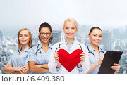 Купить «smiling female doctor and nurses with red heart», фото № 6409380, снято 1 декабря 2013 г. (c) Syda Productions / Фотобанк Лори