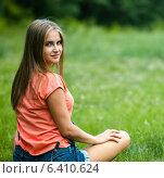 Купить «Симпатичная девушка в шортах сидит на зелёной траве и смотрит назад», эксклюзивное фото № 6410624, снято 17 июля 2014 г. (c) Игорь Низов / Фотобанк Лори