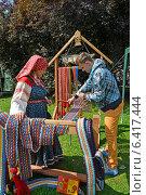 Купить «Ткачиха в народном костюме учит молодого мужчину ткать с помощью бердо. Ярмарка народного творчества», фото № 6417444, снято 15 августа 2014 г. (c) Ирина Борсученко / Фотобанк Лори