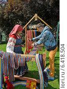 Купить «Ткачиха в народном костюме учит молодого мужчину ткать с помощью бердо. Ярмарка народного творчества», фото № 6418504, снято 15 августа 2014 г. (c) Ирина Борсученко / Фотобанк Лори