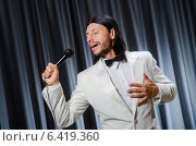Купить «Man singing in front of curtain in karaoke concept», фото № 6419360, снято 14 июля 2014 г. (c) Elnur / Фотобанк Лори