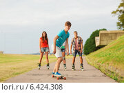 Купить «group of smiling teenagers with roller-skates», фото № 6424308, снято 10 августа 2014 г. (c) Syda Productions / Фотобанк Лори