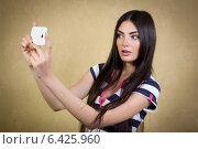 Купить «Очаровательная темноволосая девушка фотографирует сама себя с помощью телефона (делает селфи)», фото № 6425960, снято 30 июля 2014 г. (c) Михаил Гойко / Фотобанк Лори