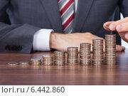 Купить «Businessman Stacking Coins In Increasing Order At Desk», фото № 6442860, снято 6 мая 2014 г. (c) Андрей Попов / Фотобанк Лори