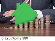 Купить «Businessman With Coin Stacks By House Model At Desk», фото № 6442880, снято 6 мая 2014 г. (c) Андрей Попов / Фотобанк Лори