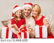 Купить «smiling family holding gift boxes and sparkles», фото № 6444608, снято 26 октября 2013 г. (c) Syda Productions / Фотобанк Лори