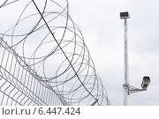 Колючая проволока на заборе с камерой видеонаблюдения. Стоковое фото, фотограф Эдуард Данилов / Фотобанк Лори