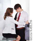 Купить «Businesswoman Undressing Male Colleague At Desk», фото № 6455716, снято 23 февраля 2014 г. (c) Андрей Попов / Фотобанк Лори