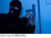 Купить «Thief Opening House Door With Tool», фото № 6459412, снято 18 января 2014 г. (c) Андрей Попов / Фотобанк Лори