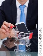 Купить «Businessman Pushing Smartphone In Shopping Cart», фото № 6459516, снято 18 января 2014 г. (c) Андрей Попов / Фотобанк Лори