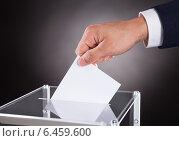 Купить «Businessman Inserting Ballot In Box On Desk», фото № 6459600, снято 10 апреля 2014 г. (c) Андрей Попов / Фотобанк Лори