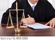 Купить «Judge Signing Document At Table In Courtroom», фото № 6459680, снято 10 апреля 2014 г. (c) Андрей Попов / Фотобанк Лори