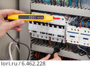 Купить «Electrician Examining Fusebox With Voltage Tester», фото № 6462228, снято 20 апреля 2014 г. (c) Андрей Попов / Фотобанк Лори