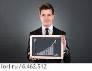 Купить «Businessman Holding Slate With Growing Bar Graph», фото № 6462512, снято 28 июня 2014 г. (c) Андрей Попов / Фотобанк Лори