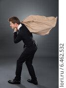 Купить «Businessman Carrying Moneybag», фото № 6462532, снято 28 июня 2014 г. (c) Андрей Попов / Фотобанк Лори