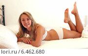 Купить «Cheerful long-haired woman wearing underwear posing on bed», видеоролик № 6462680, снято 29 сентября 2014 г. (c) Яков Филимонов / Фотобанк Лори