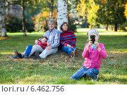 Ребенок сидит перед камерой с телефоном в руках, семья на заднем плане не в фокусе. Стоковое фото, фотограф Кекяляйнен Андрей / Фотобанк Лори