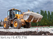 Купить «Тяжелый трактор работает на строительстве дороги», фото № 6470716, снято 22 апреля 2018 г. (c) FotograFF / Фотобанк Лори