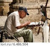 Пожилой художник рисует на улице Кубинского города Гавана (2014 год). Редакционное фото, фотограф Александра / Фотобанк Лори