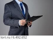 Мужчина в деловом костюме держит планшетник для бумаг. Стоковое фото, фотограф Людмила Дутко / Фотобанк Лори