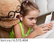 Купить «Девочка в наушниках с игрушечным медведем смотрят в мобильный телефон», фото № 6515404, снято 9 октября 2014 г. (c) Элина Гаревская / Фотобанк Лори