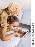 Купить «Девочка в наушниках с игрушечным медведем смотрят в мобильный телефон», фото № 6521364, снято 9 октября 2014 г. (c) Элина Гаревская / Фотобанк Лори