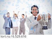 Купить «Close up of a man dressed in a suit smiling and holding a cup with people cheerin», фото № 6529616, снято 27 марта 2019 г. (c) Wavebreak Media / Фотобанк Лори