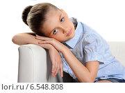 Красивая девочка в синей рубашке сидит на кресле на белом фоне. Стоковое фото, фотограф Сергей Богданов / Фотобанк Лори